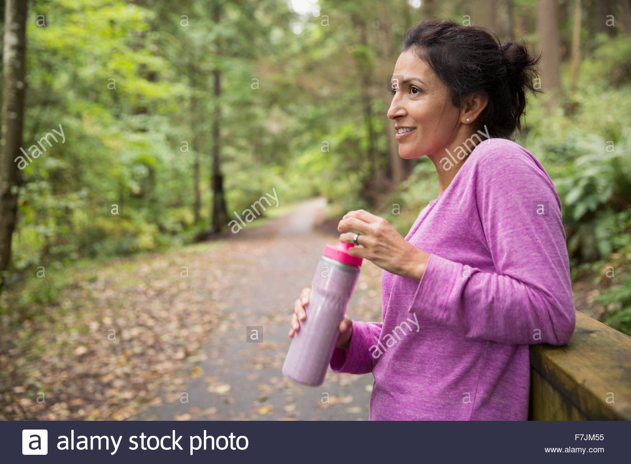 Smiling woman taking a break drinking water woods - Stock Image