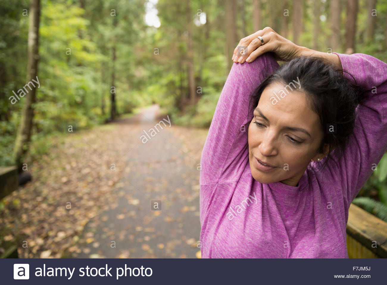 Woman stretching arms preparing for run in woods - Stock Image