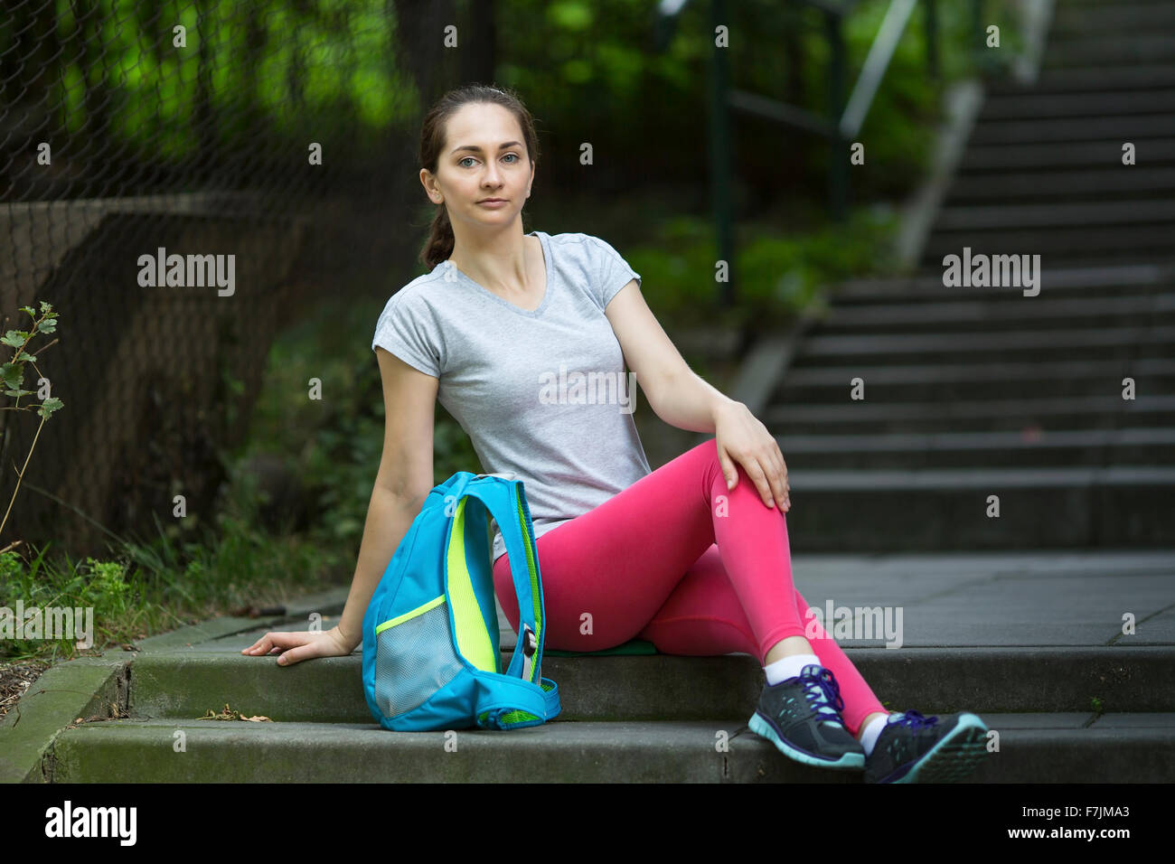 Young sporty girl sitting on the steps outdoors. - Stock Image