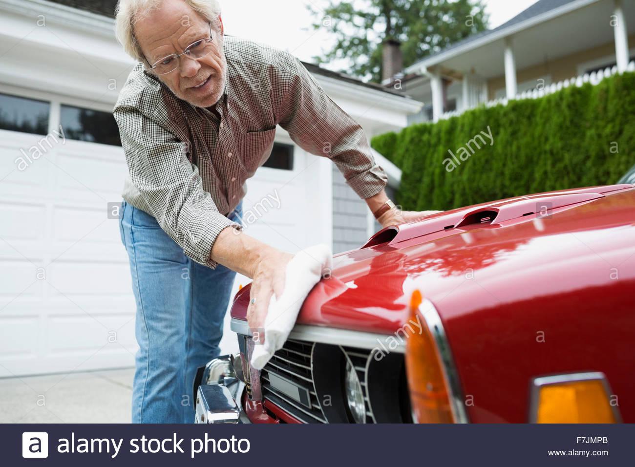 Senior man waxing classic car in driveway - Stock Image