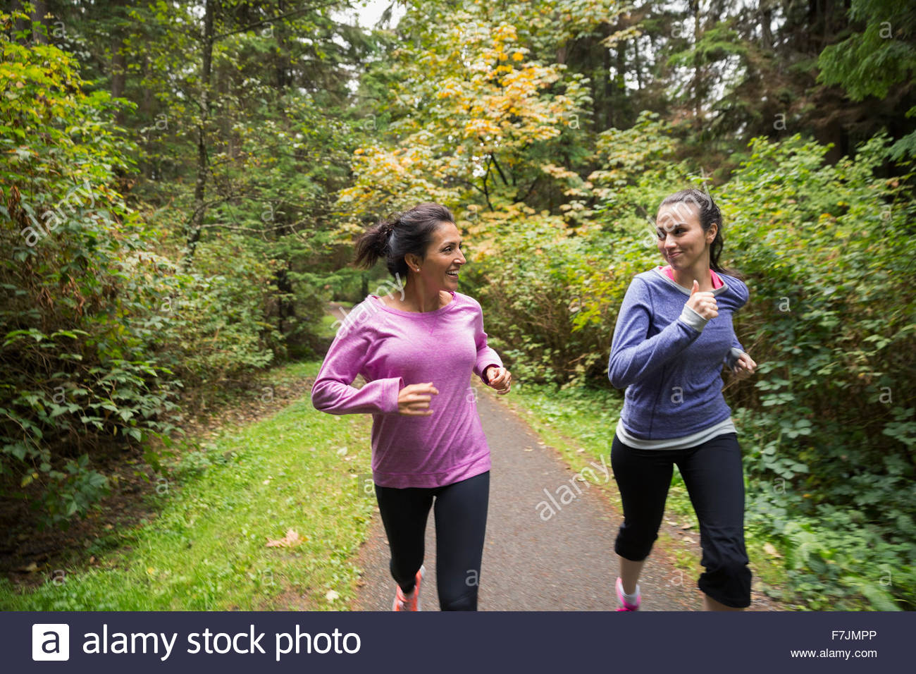 Mother and daughter jogging on path in woods - Stock Image