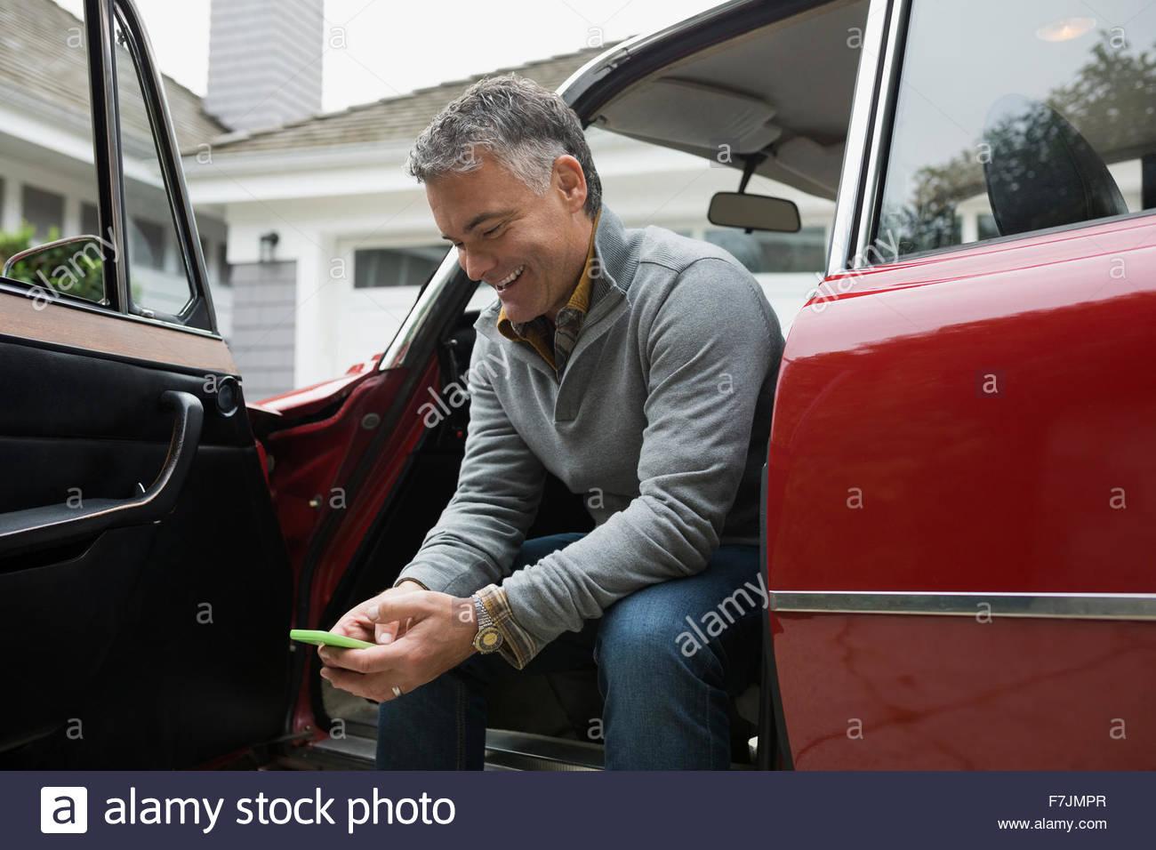 Man using cell phone in car door open - Stock Image