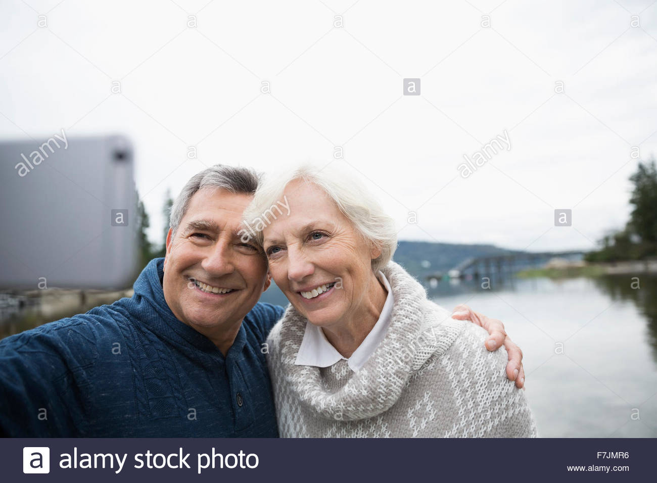 Senior couple taking selfie with lake in background - Stock Image
