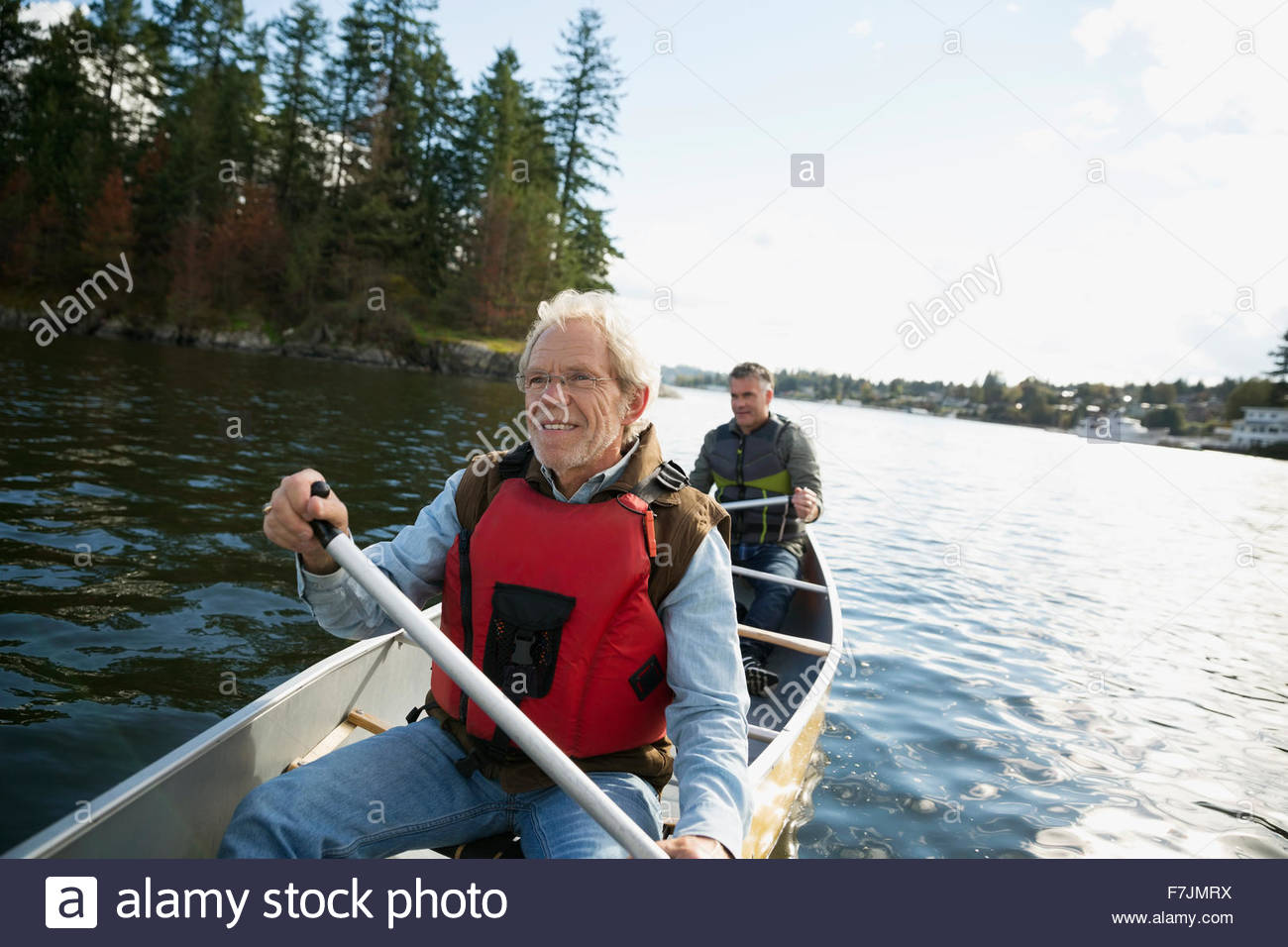 Father and son canoeing on lake - Stock Image
