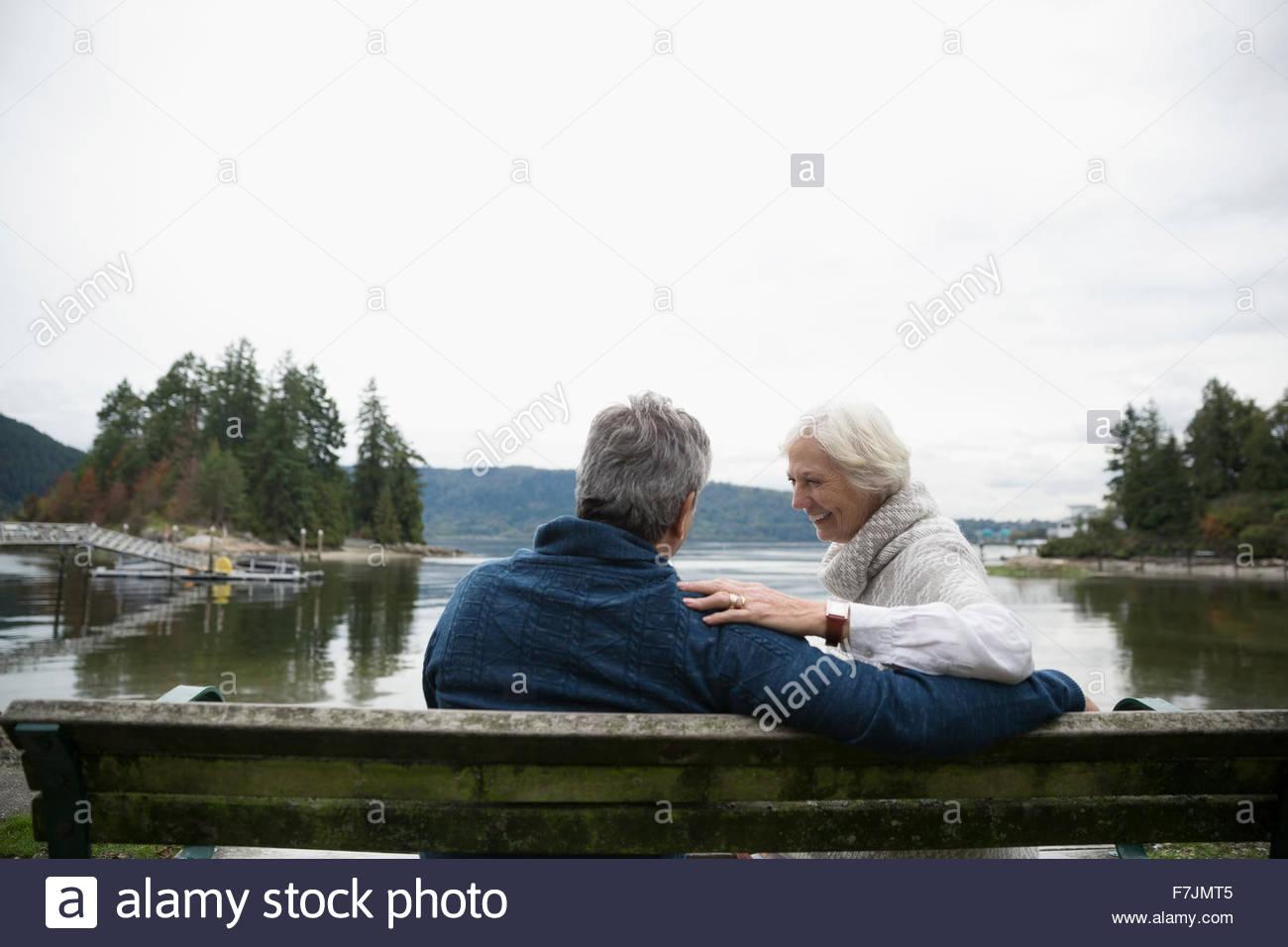 Senior couple laughing on bench overlooking lake - Stock Image