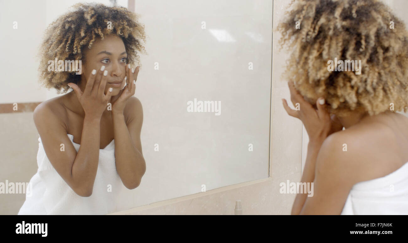 Woman Viewing Herself In The Mirror - Stock Image