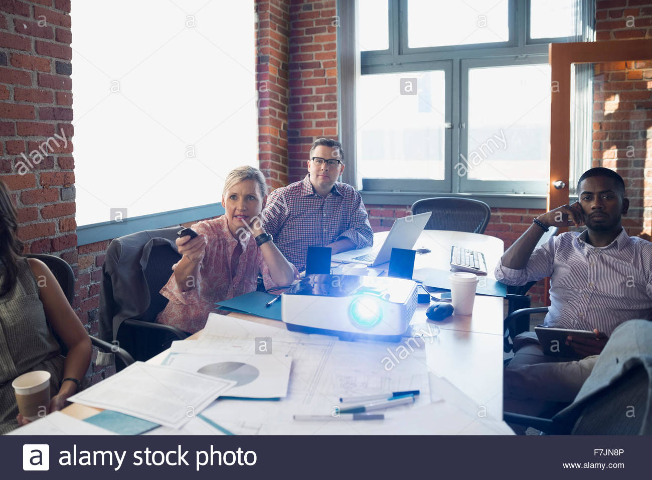 Business people using projector in conference room meeting - Stock Image