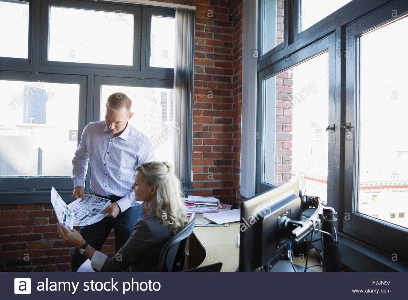 Business people reviewing proofs in office - Stock Image