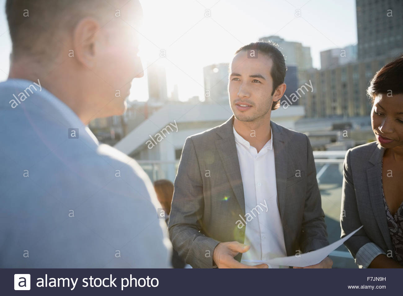 Business people discussing paperwork on sunny urban rooftop - Stock Image