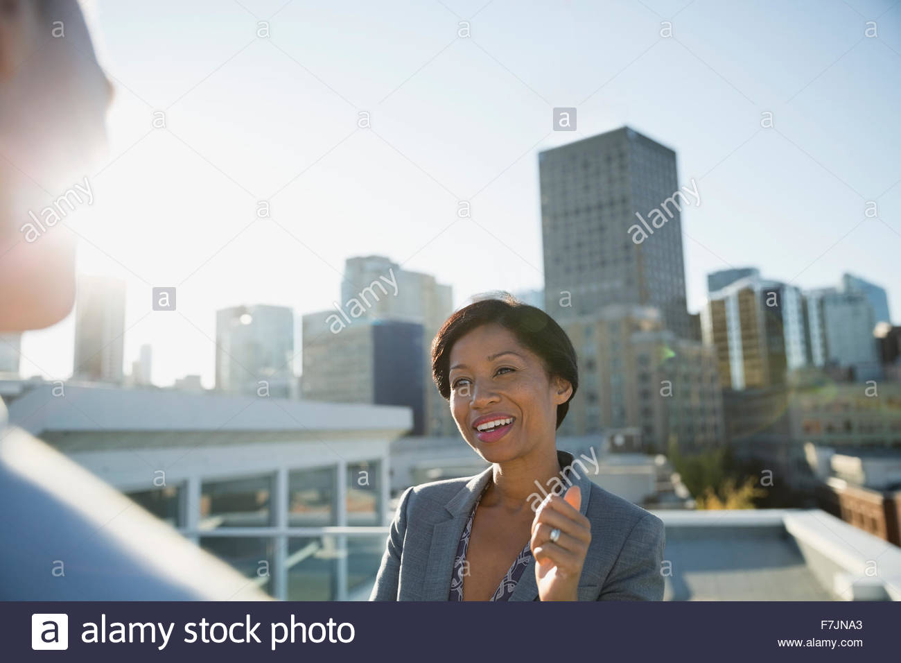 Business people talking on sunny urban rooftop - Stock Image