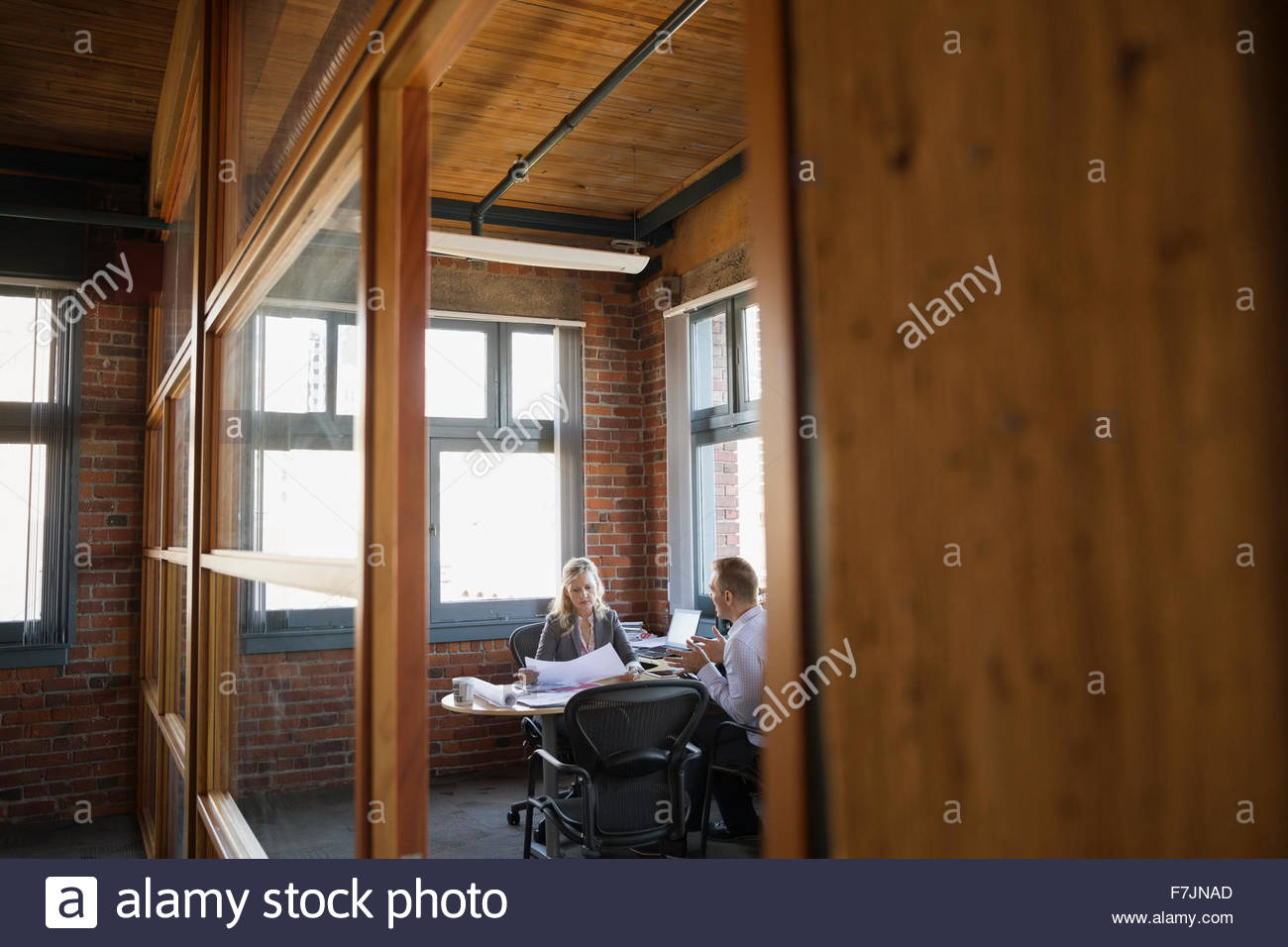 Business people discussing paperwork in office - Stock Image