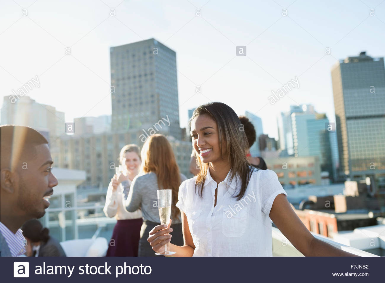 Smiling business people drinking champagne on urban rooftop - Stock Image