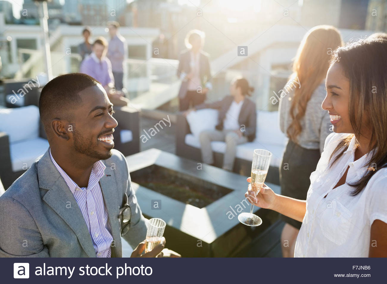Smiling business people drinking champagne on sunny rooftop - Stock Image