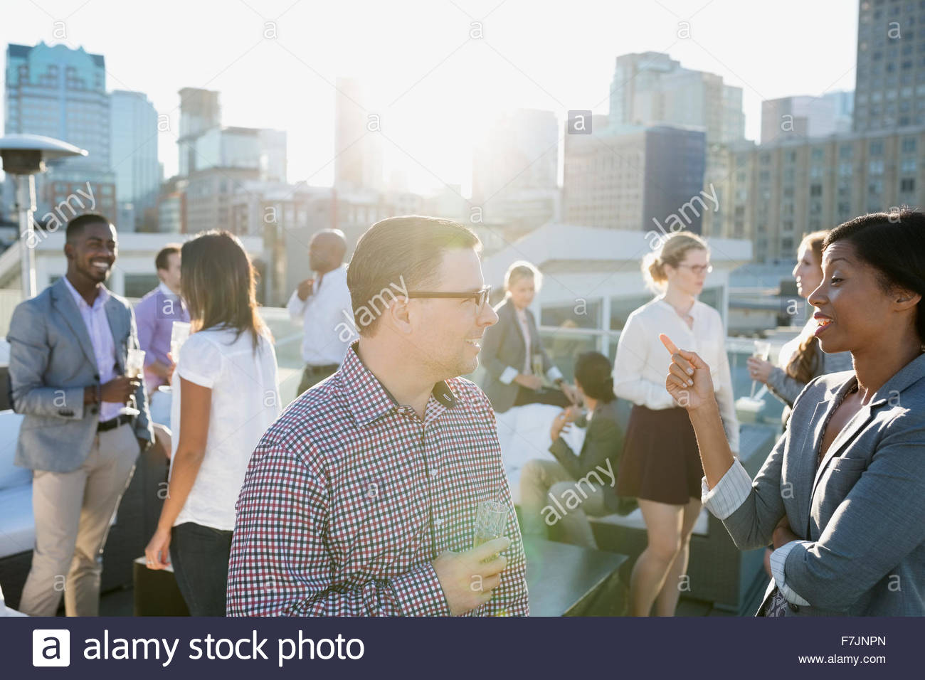 Business people drinking champagne socializing on sunny rooftop - Stock Image