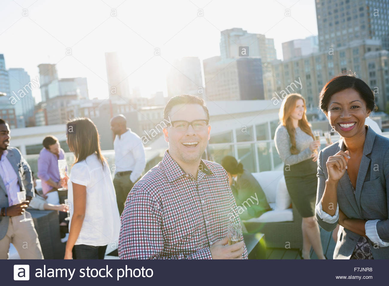 Portrait smiling business people on sunny urban rooftop - Stock Image