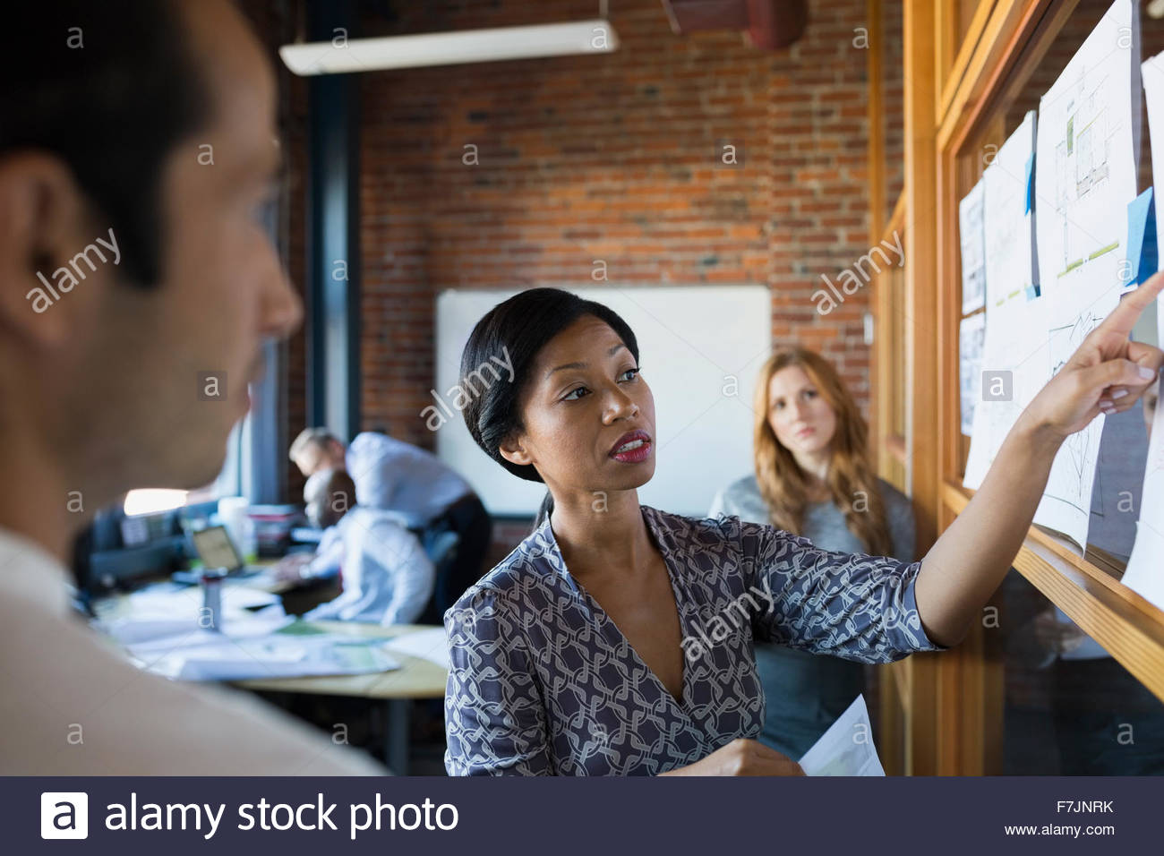 Businesswoman leading meeting pointing to paperwork - Stock Image