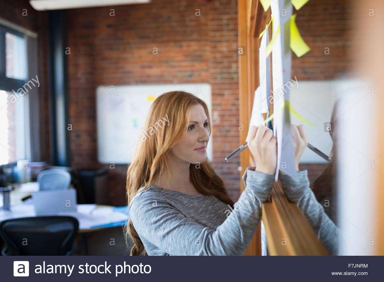Businesswoman writing on paperwork in office - Stock Image