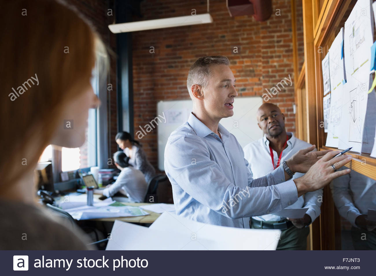Business people brainstorming with paperwork in office meeting - Stock Image