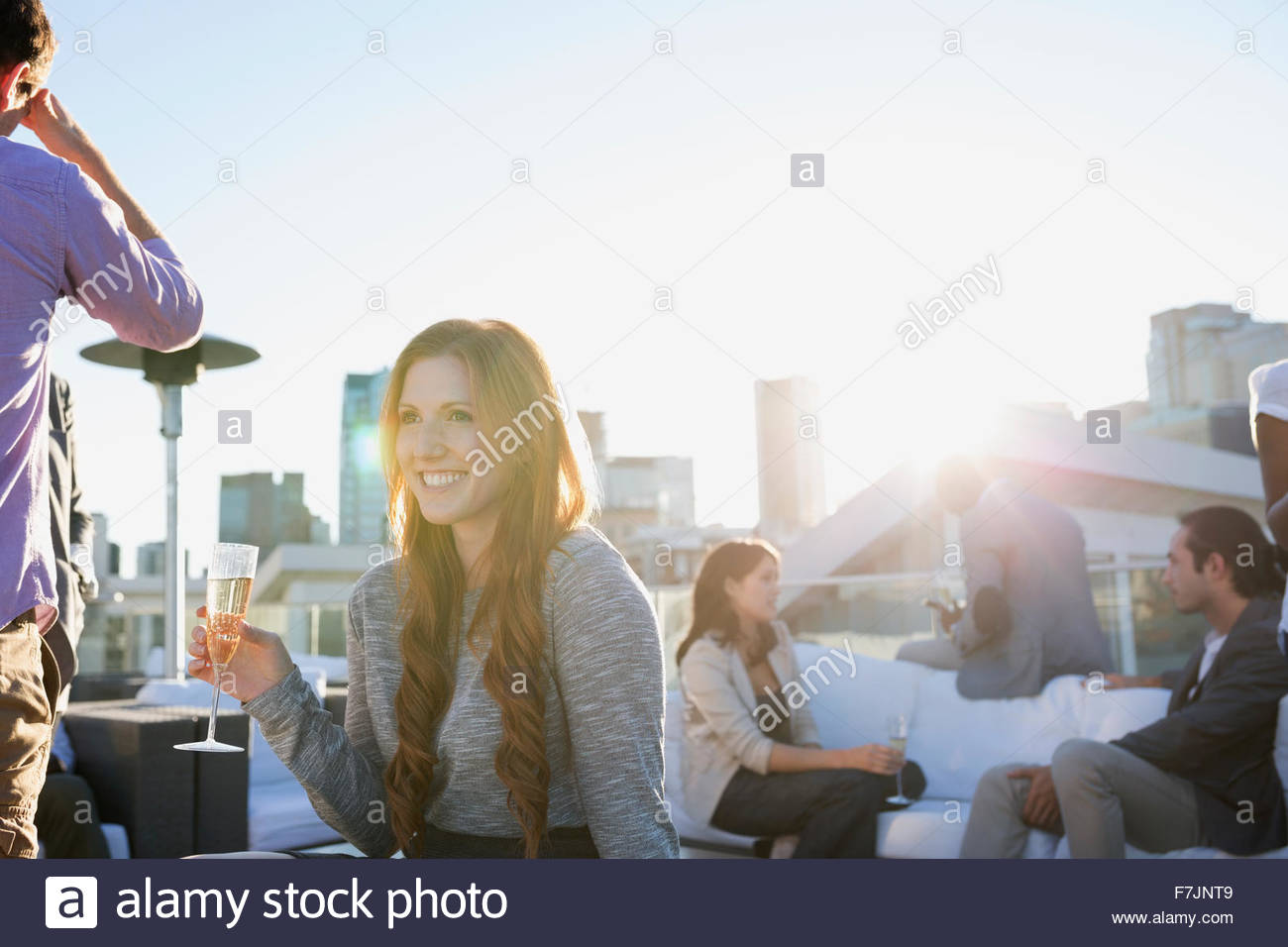 Business people drinking champagne on sunny urban rooftop - Stock Image