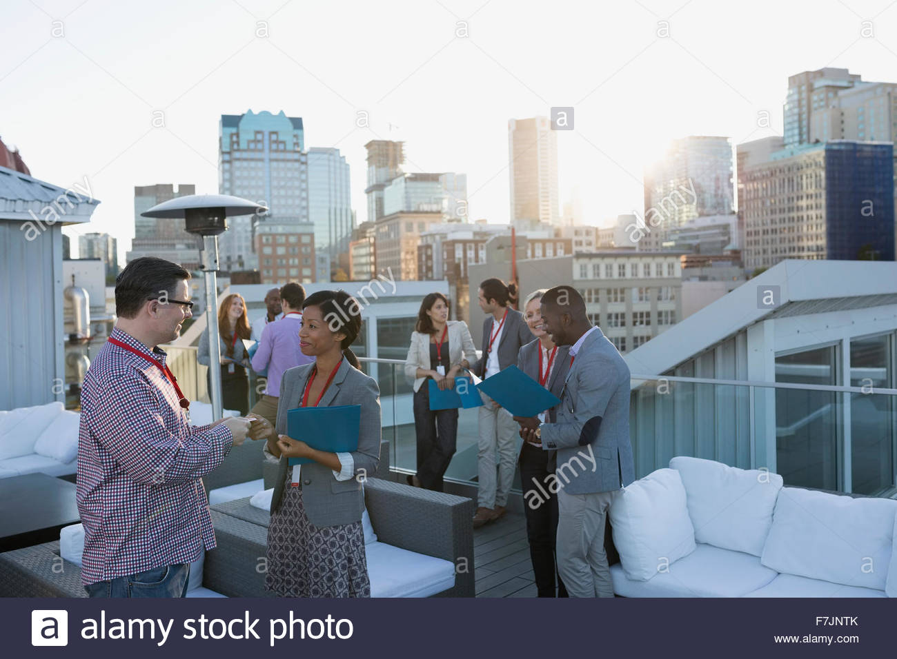 Business people networking on urban rooftop - Stock Image