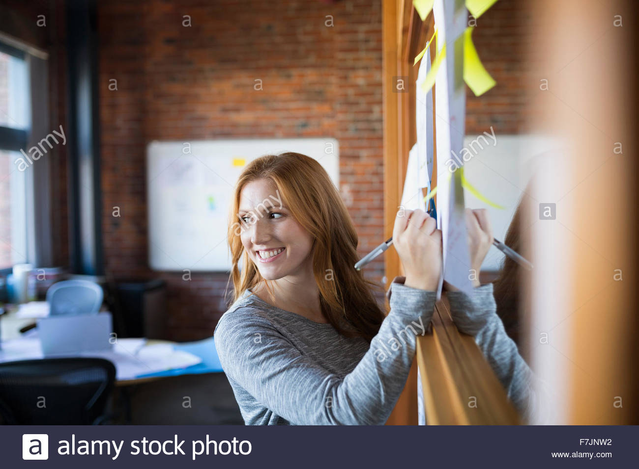 Smiling businesswoman writing on paperwork in office - Stock Image