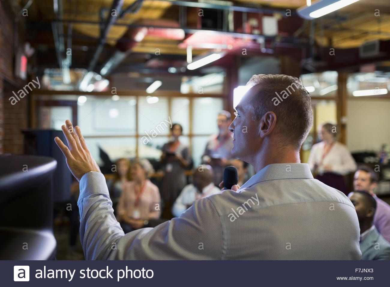 Gesturing businessman leading conference presentation - Stock Image
