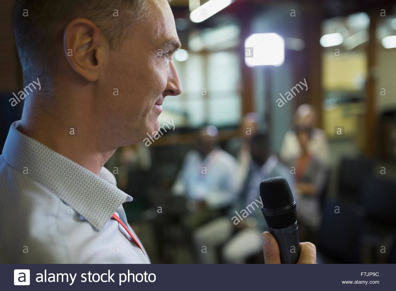 Close up businessman with microphone speaking at conference - Stock Image