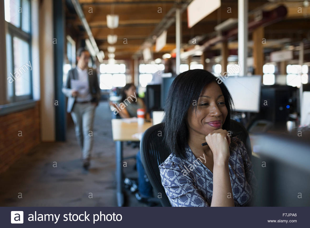 Smiling businesswoman working in office - Stock Image