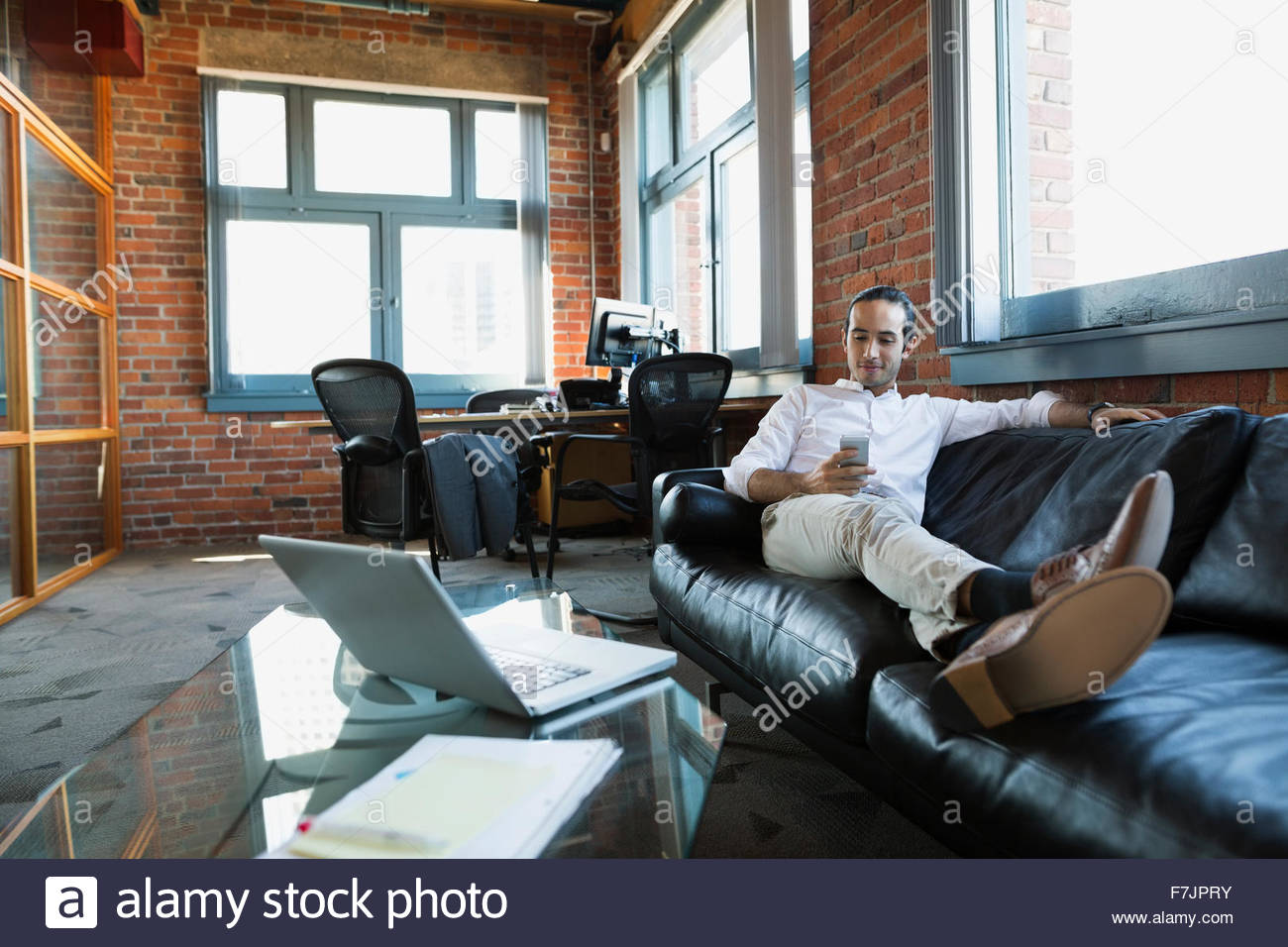 Comfortable businessman texting on office sofa - Stock Image