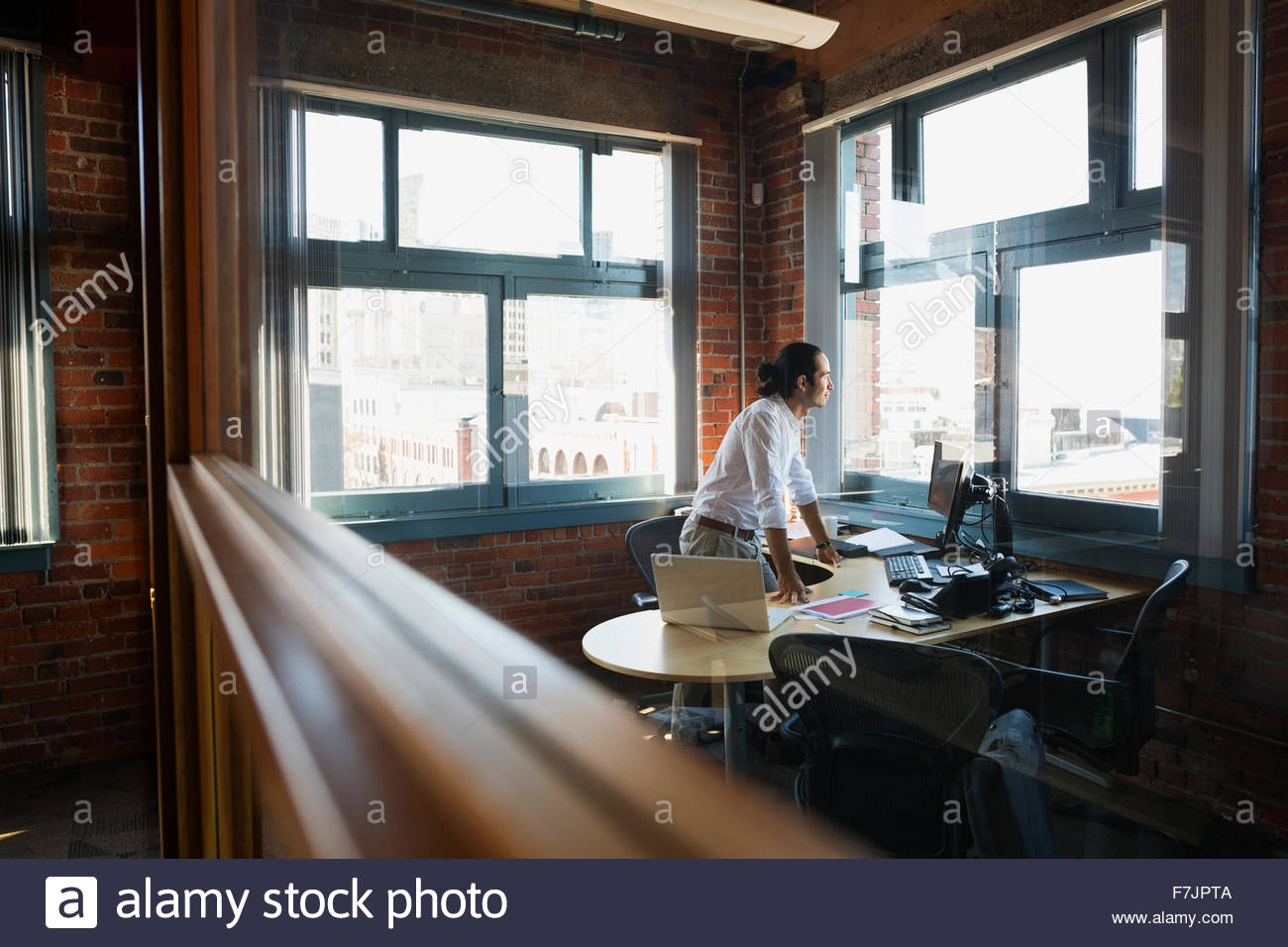 Pensive businessman looking out office window - Stock Image