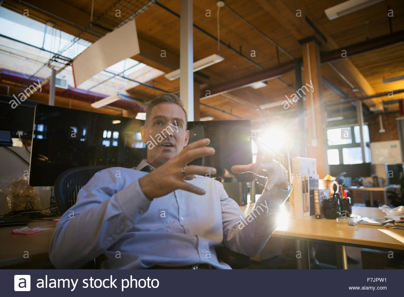 Businessman gesturing in office - Stock Image