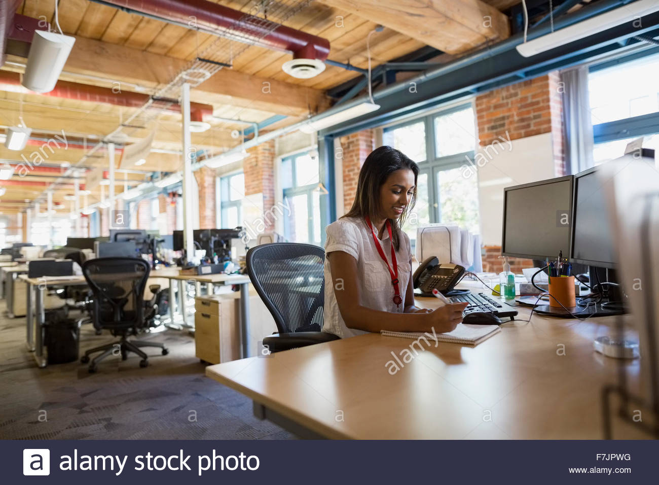 Businesswoman writing at office desk - Stock Image