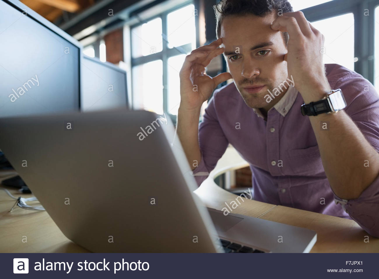 Stressed businessman working at laptop in office - Stock Image