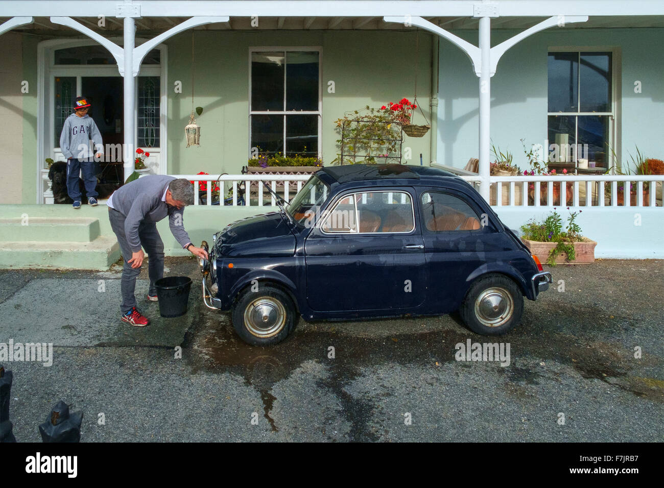 man male wash washing fiat 500 bambina car vehicle - Stock Image