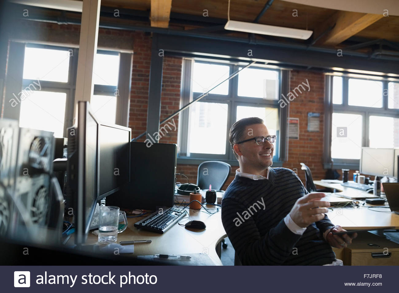 Smiling businessman gesturing in office - Stock Image