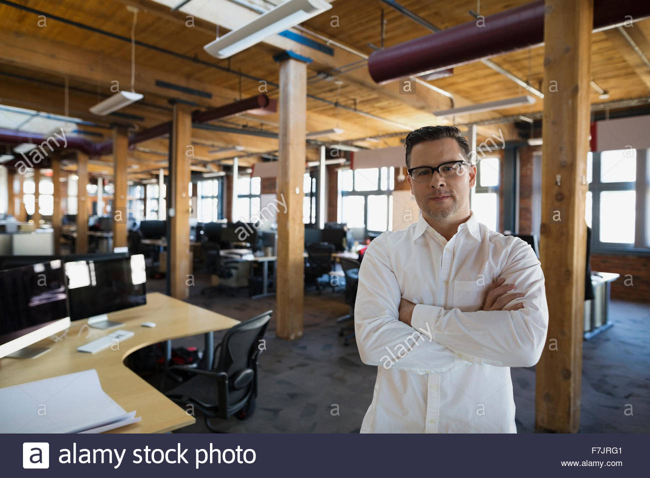 Portrait confident businessman arms crossed in open office - Stock Image