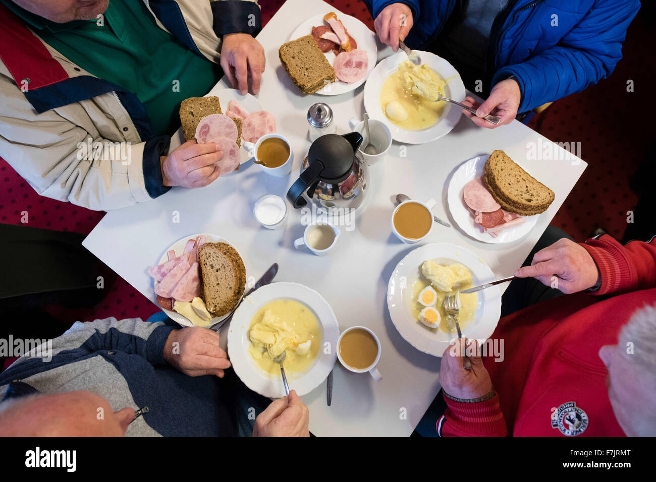 Berlin, Germany. 01st Dec, 2015. People in need eat at a table in the warm room of the aid organisation Caritas - Stock Image