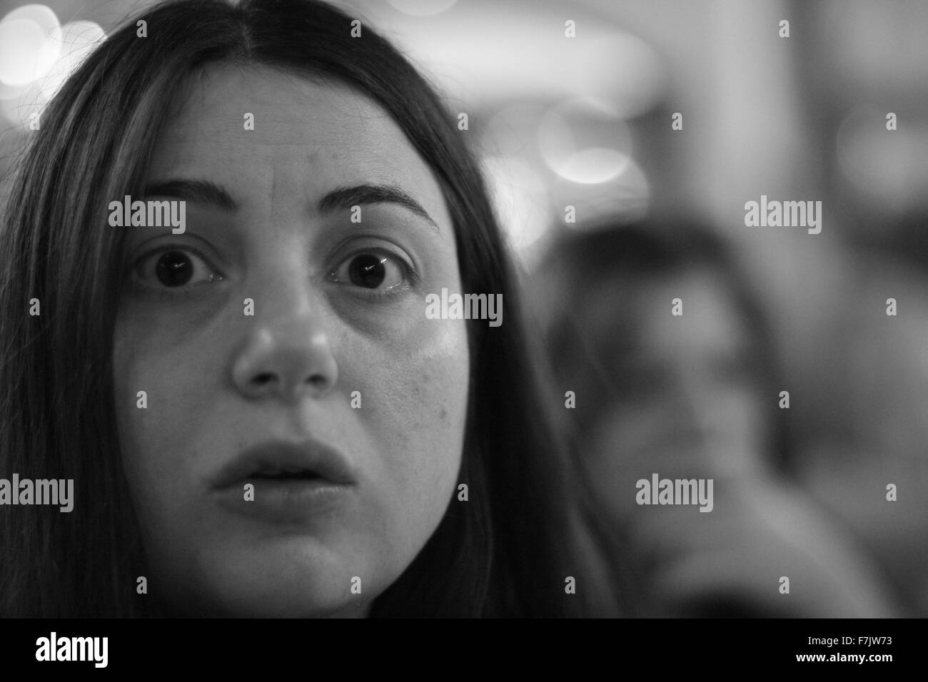 Young woman with surprised / concerned look staring at the camera with blurred background in black and white - Stock Image