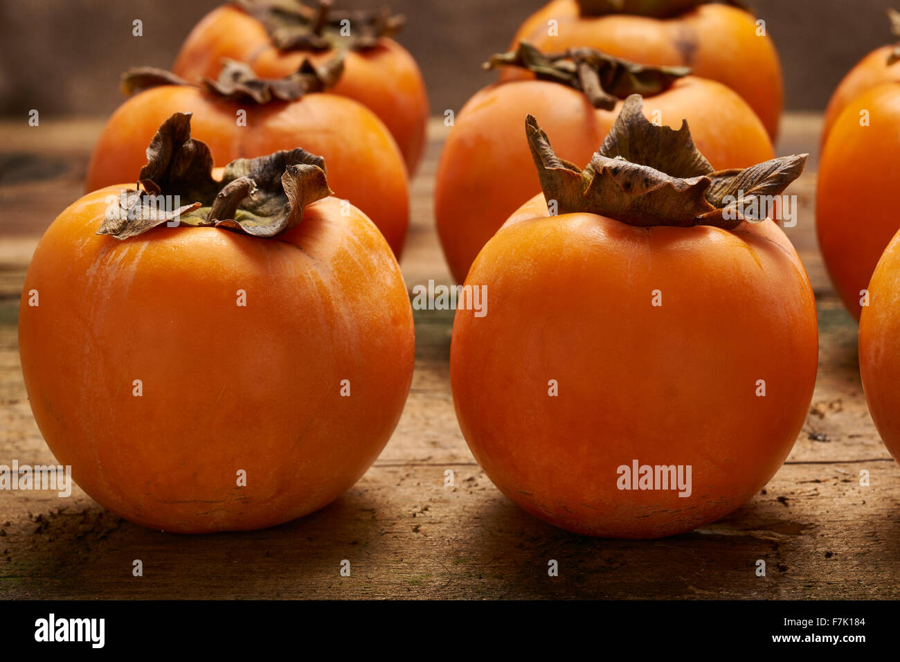 yummy orange persimmons propped up an old wooden table - Stock Image
