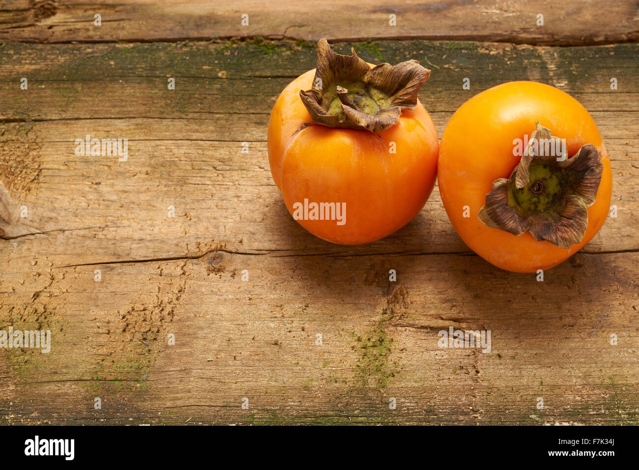 two delicious orange persimmon on an old wooden table Stock Photo