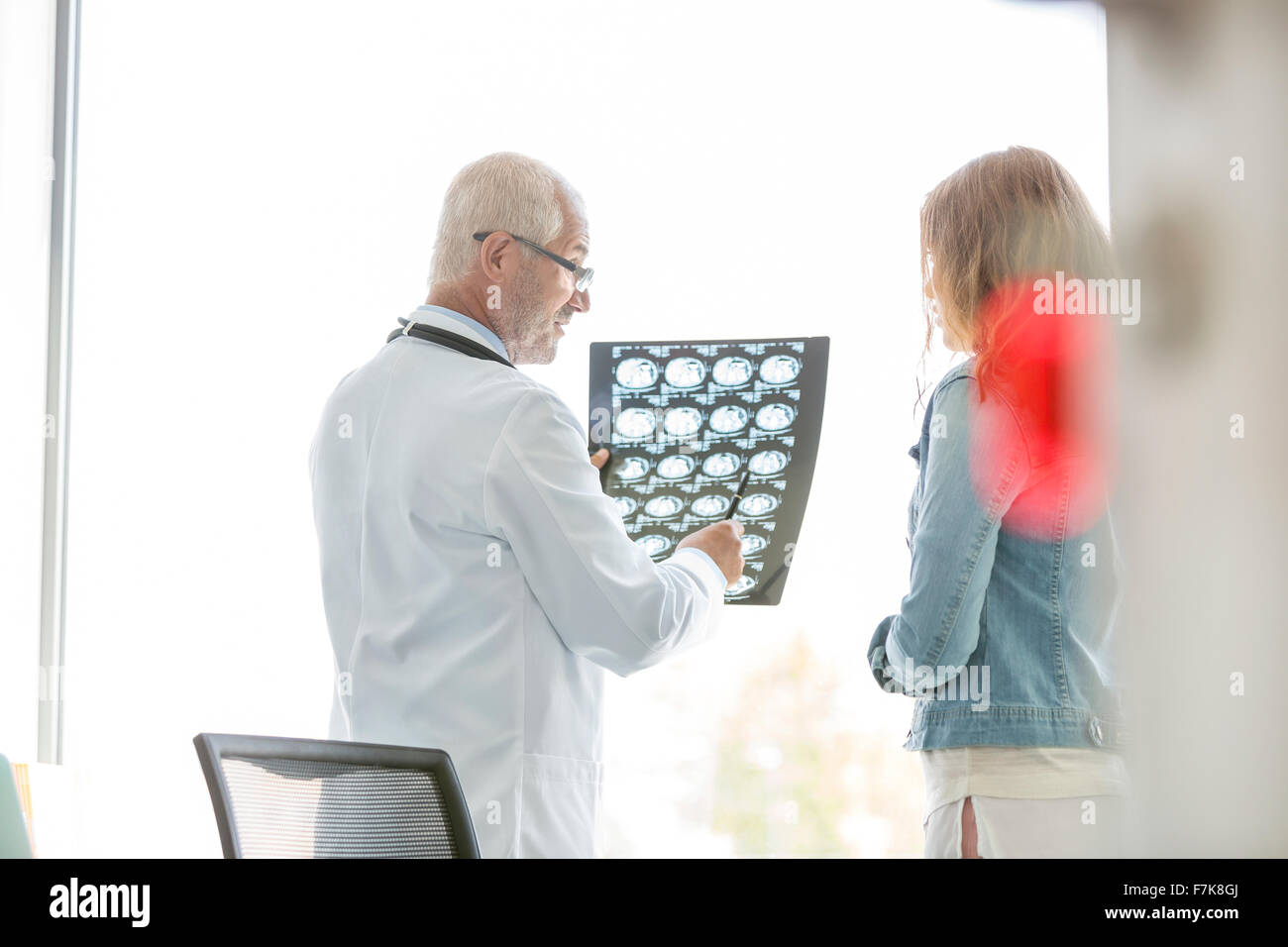 Doctor reviewing x-rays with patient in doctor's office - Stock Image