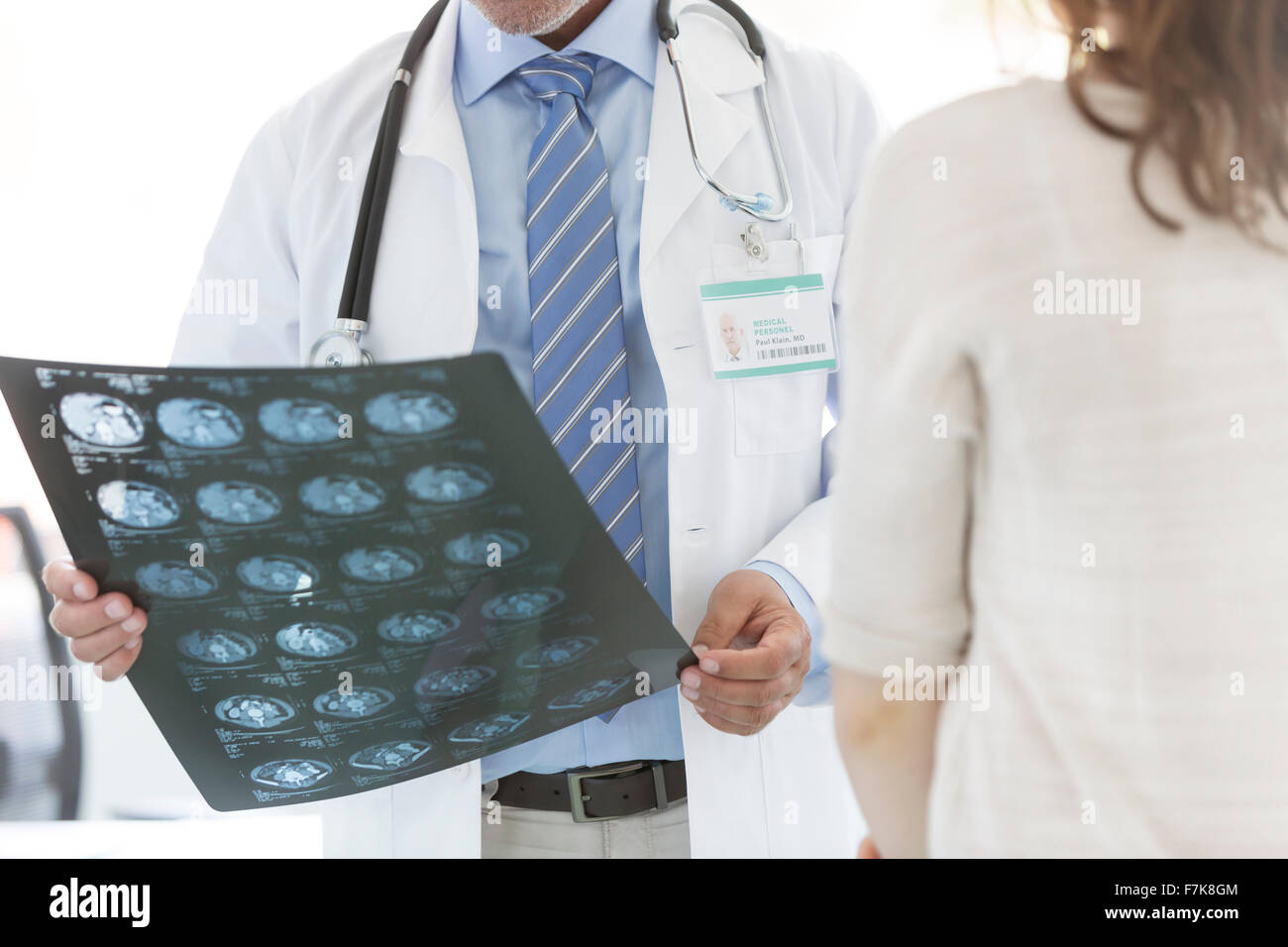 Doctor reviewing x-rays with patient - Stock Image