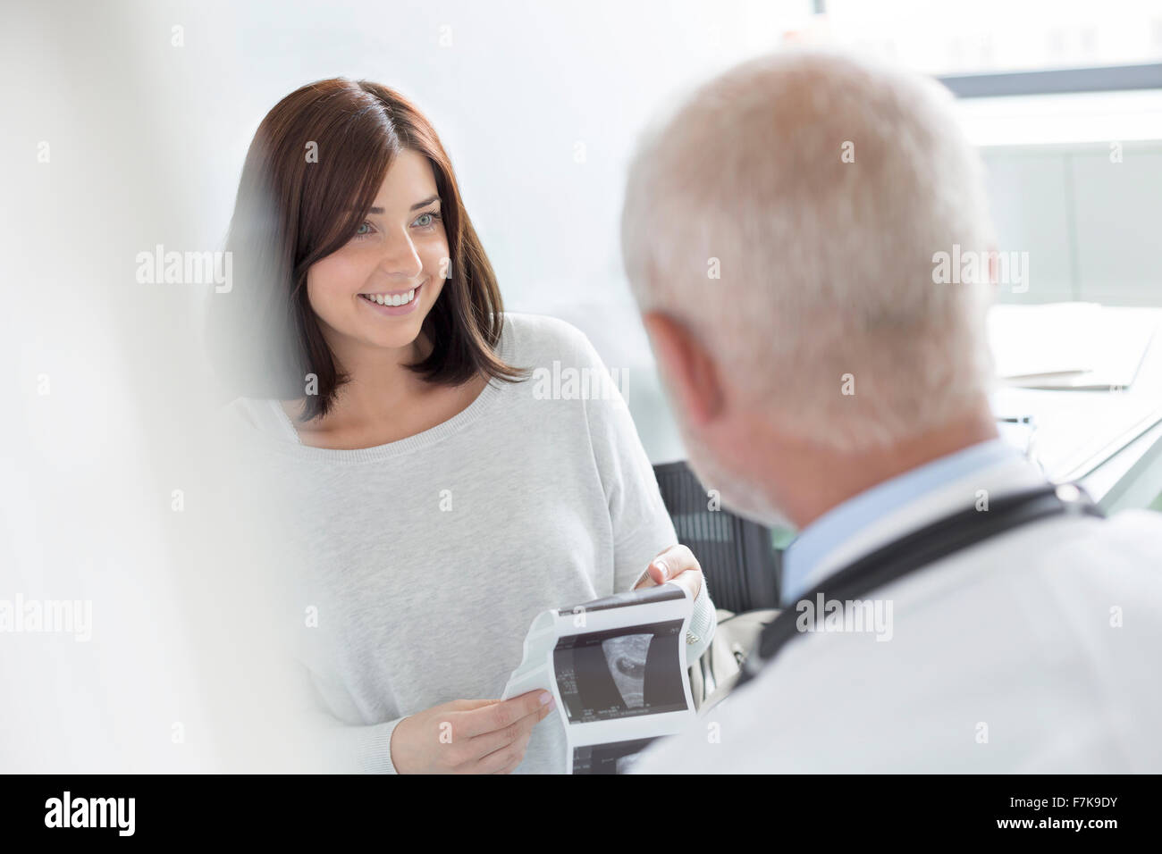 Doctor and patient looking at ultrasound x-rays in doctor's office - Stock Image