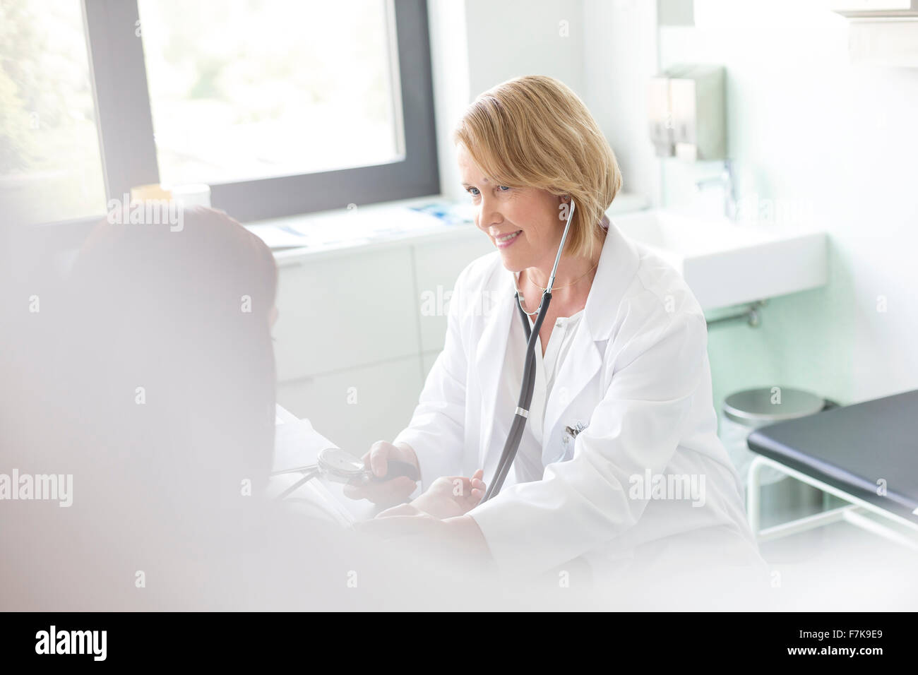 Doctor checking patient's blood pressure in examination room - Stock Image
