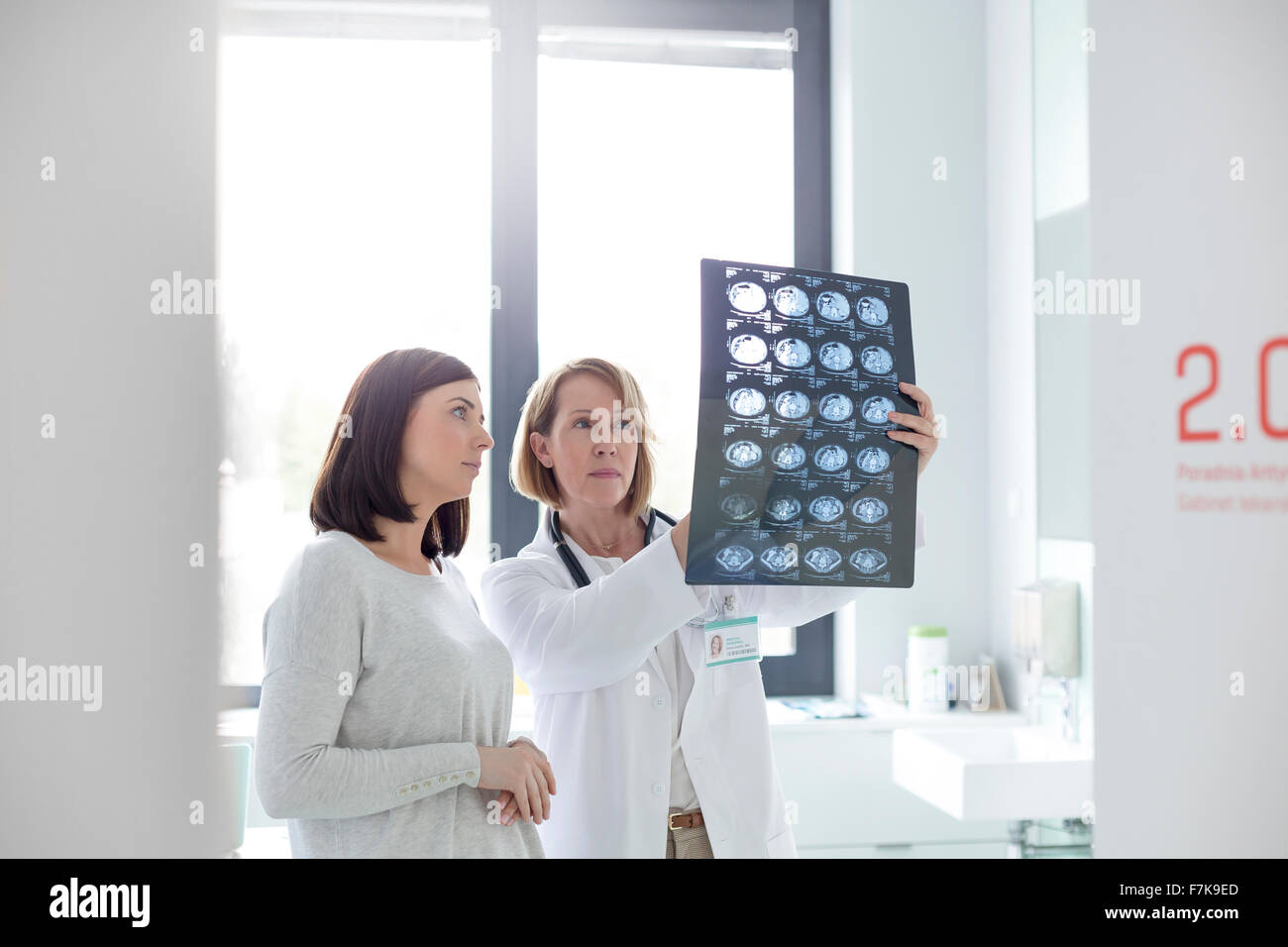 Serious doctor and patient reviewing x-rays in examination room - Stock Image