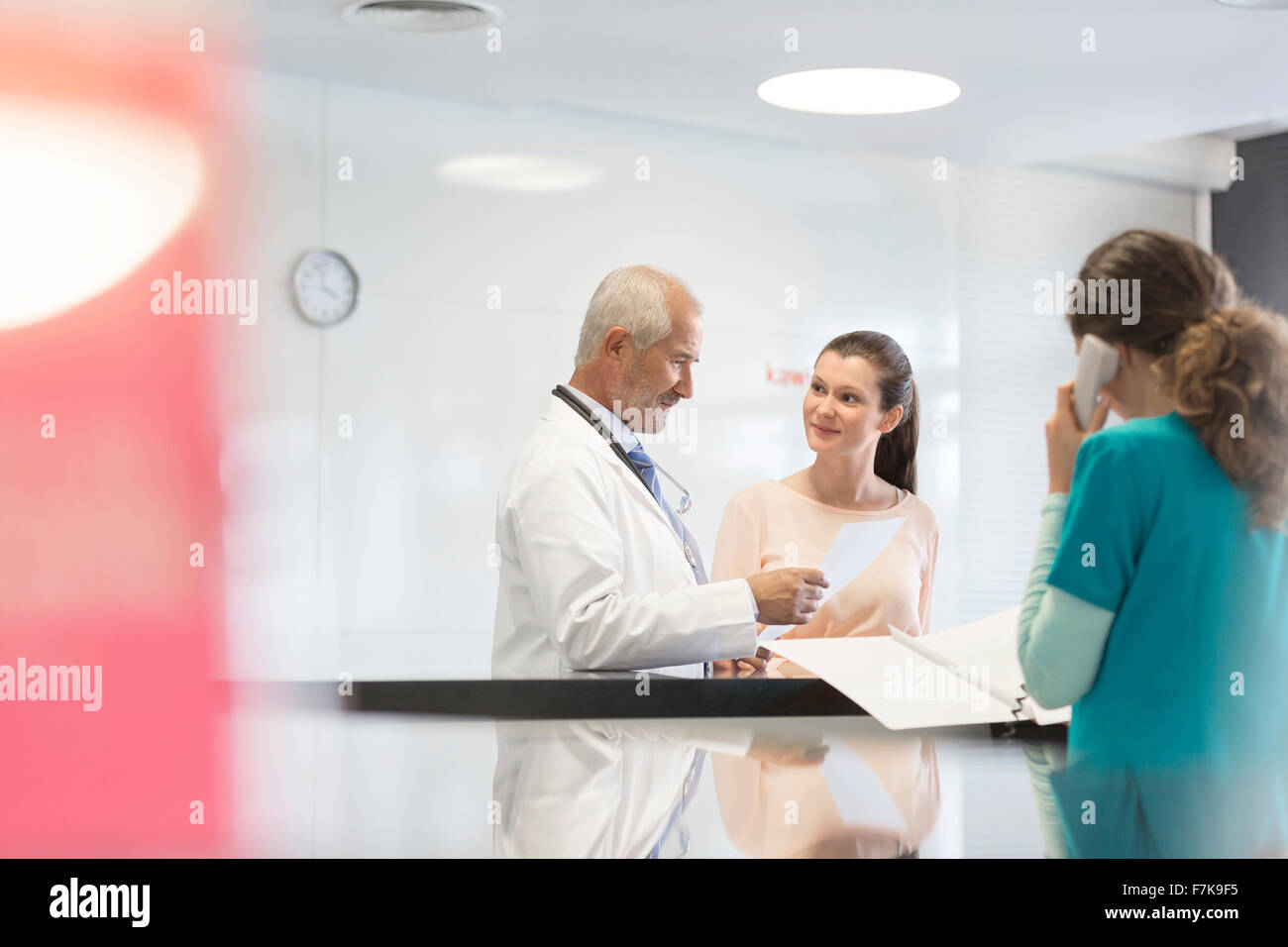Doctor and patient discussing medical record at nurses station - Stock Image