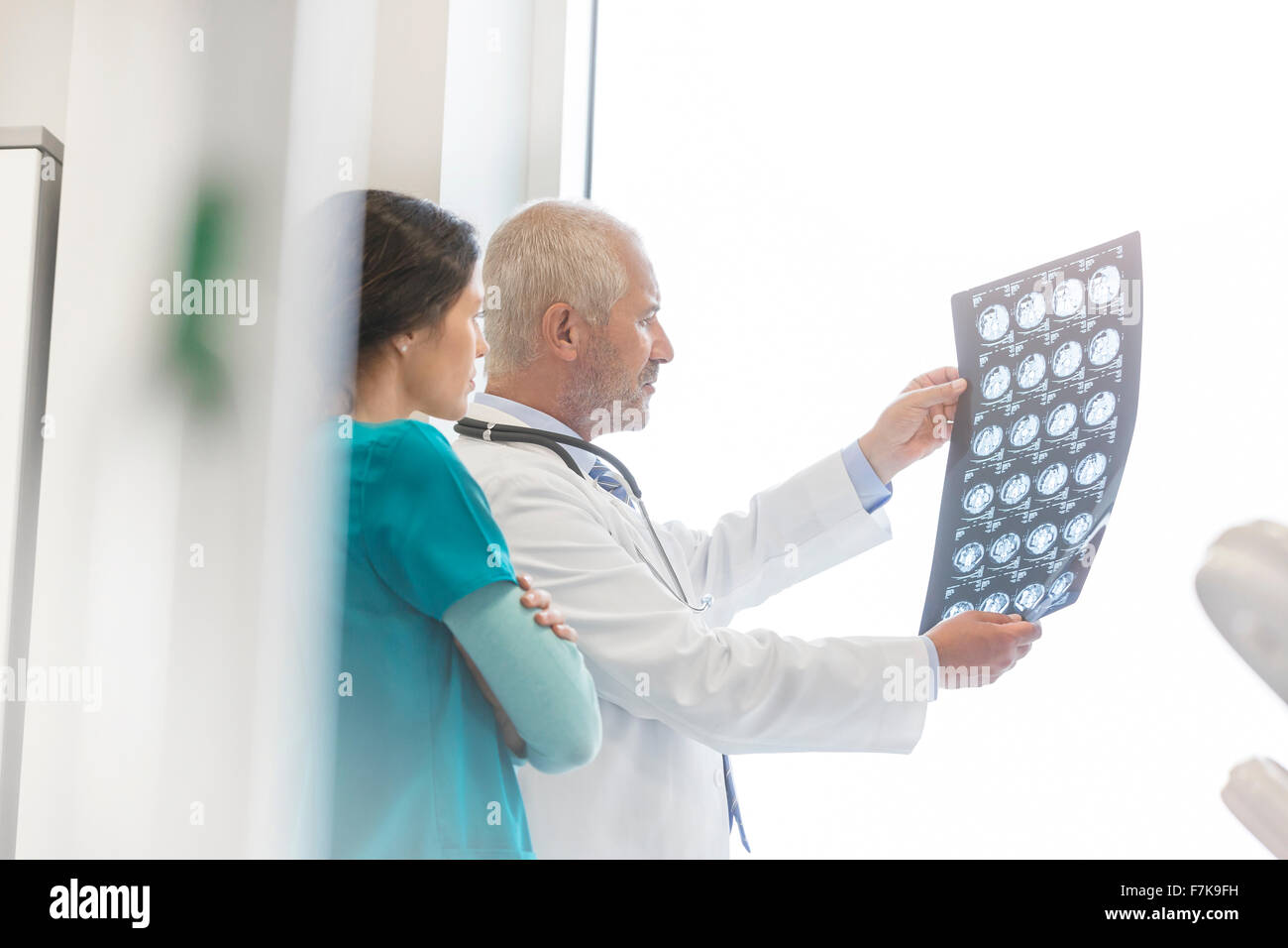 Doctor and nurse reviewing x-rays in doctor's office - Stock Image