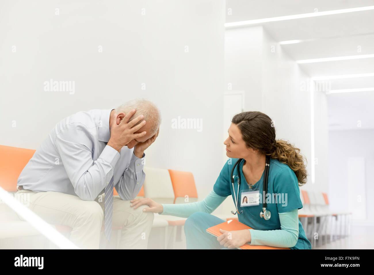Nurse consoling upset man in clinic corridor - Stock Image