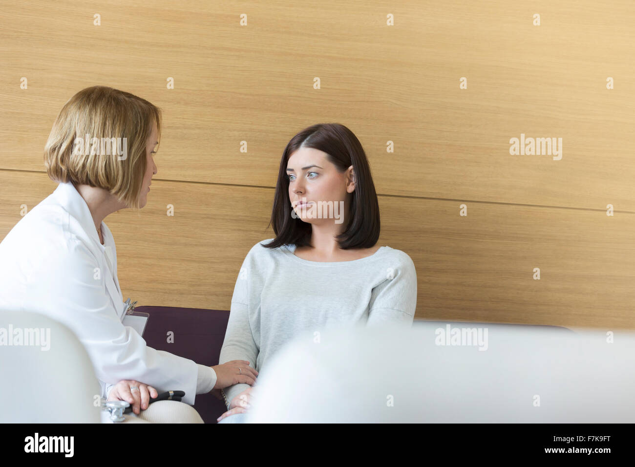 Doctor consoling serious patient in clinic lobby - Stock Image