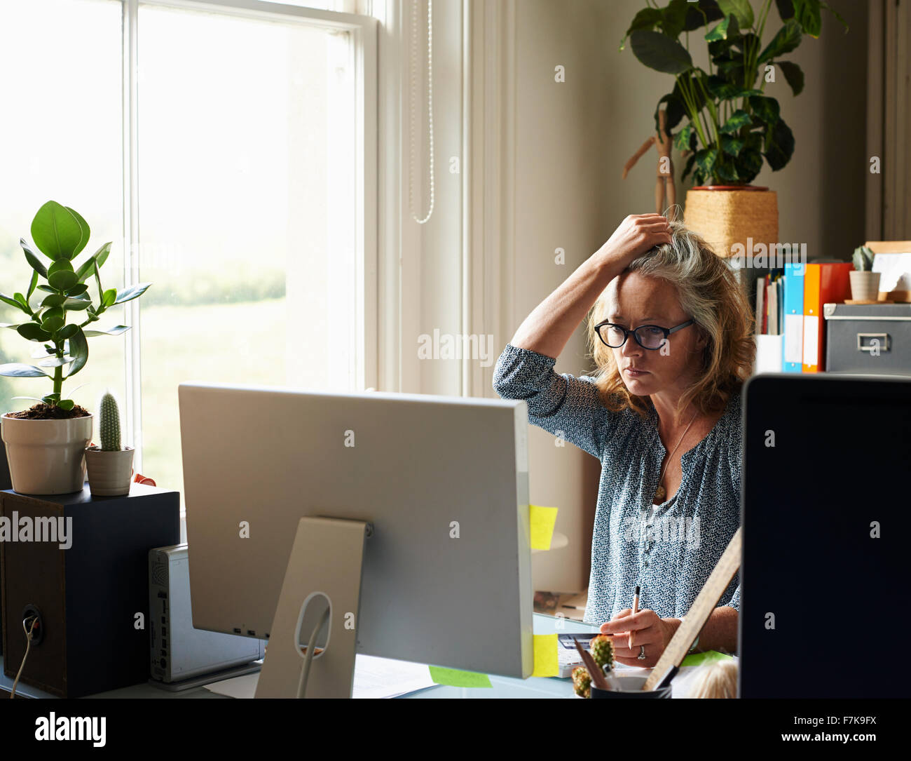 Stressed woman with hand in hair holding credit card at computer in home office - Stock Image